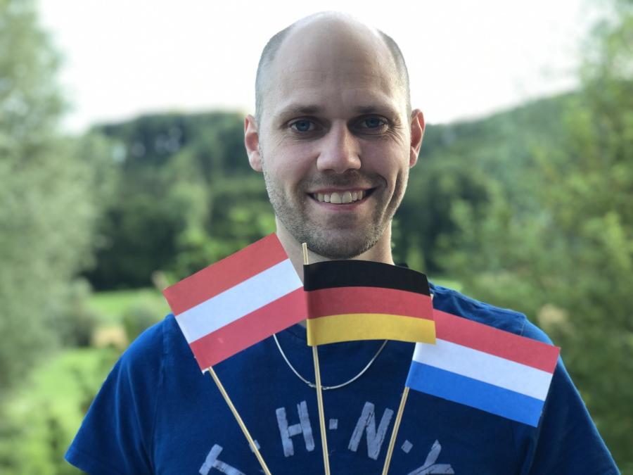 Theaterautor Atréju Diener mit den Landesflaggen von Österreich, Deutschland und Luxemburg Plausus Verlag.